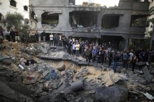 Palestinians gather around destroyed house after an Israeli air strike in Gaza City